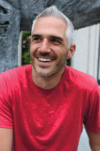 Communication & Intimacy coach Shaun Galanos smiling in a red T Shirt